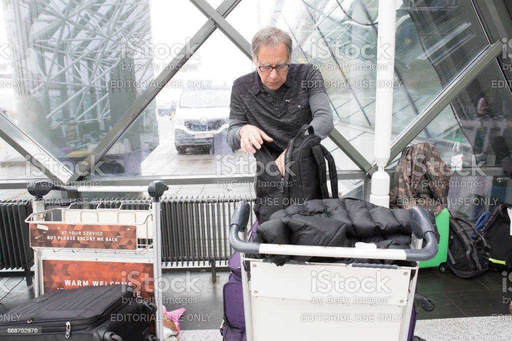 Homem caucasiano sênior, olhando para dentro de sua mochila em pé com sua bagagem no Aeroporto Internacional de Keflavík, Islândia - foto de acervo