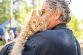 istock Senior Caucasian Man Playing with a Ginger Kitten in Urals, Russia 1166213857