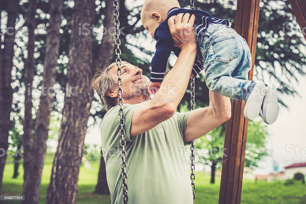 Senior caucasian man playing with his grandson in city park stock photo