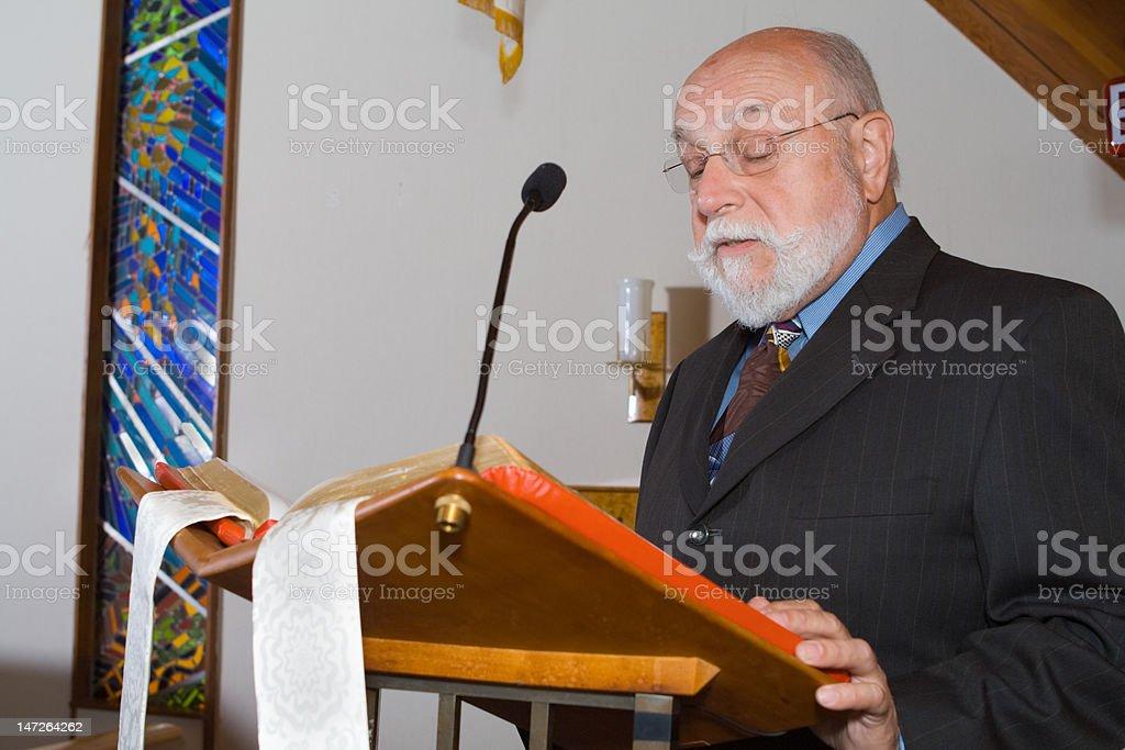Senior Caucasian Man Reading from Bible at Podium in Church royalty-free stock photo