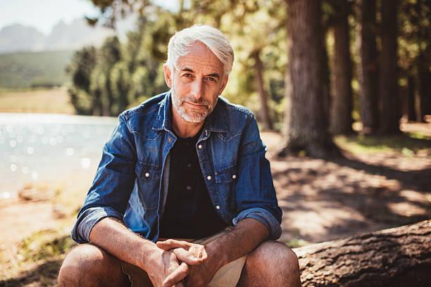 senior europäischer abstammung mann entspannend auf einem baumstamm am see - senior mann porträts stock-fotos und bilder
