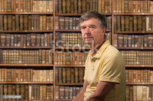 Senior old man looking at camera with a background of shelves of old books as if in library of a stately home