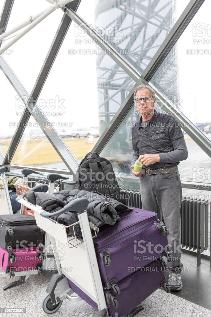Homem caucasiano sênior fica com sua bagagem no Aeroporto Internacional de Keflavík, Islândia - foto de acervo