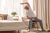 istock Senior caucasian man stretching side sitting on chair at his living room. 1319484572