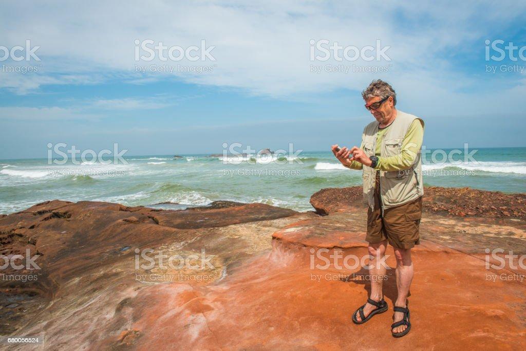 Senior Caucasian Man Surfing on Smart Phone, the Atlantic Coast, Legzira, Sidi Ifni, Morocco, North Africa stock photo