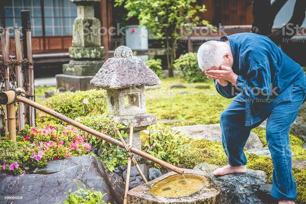 Senior Caucasian Man Washing in Buddhist Temple Garden, Kyoto, Japan Lizenzfreies stock-foto