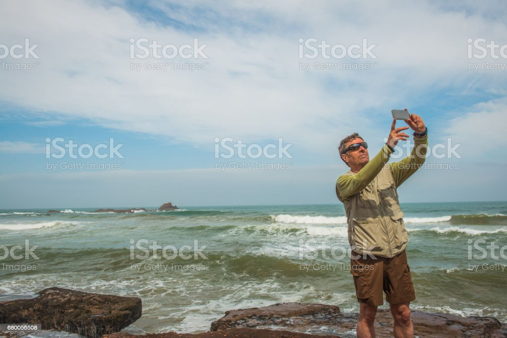 Senior Caucasian tourist on the Atlantic Coast Taking Selfie,  Legzira, Sidi Ifni, Morocco, North Africa stock photo