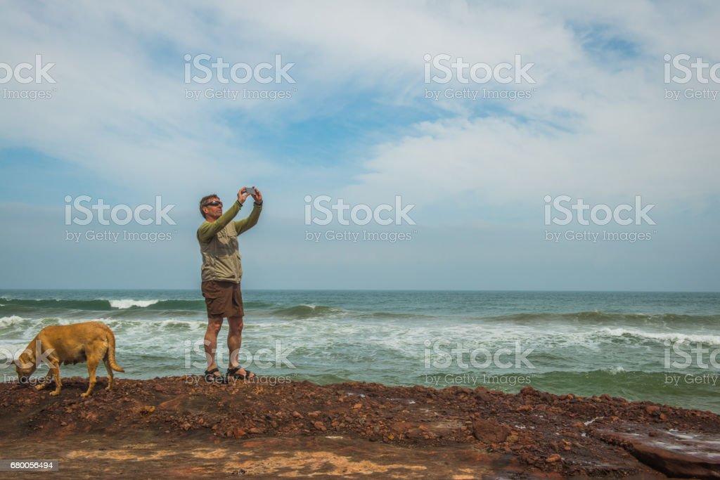 Senior Caucasian Tourist on the Atlantic Coast Taking Selfie of Himself and the Dog,  Legzira, Sidi Ifni, Morocco, North Africa stock photo