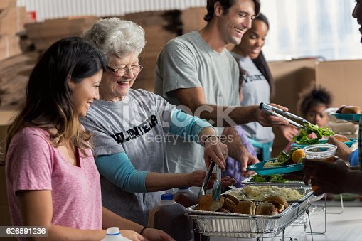 istock Senior Caucasian woman serves meal in soup kitchen 626891236