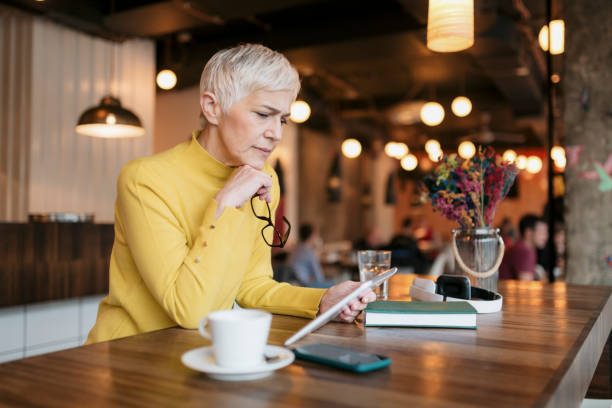 Senior Caucasian woman sitting in a coffee shop, using a digital tablet computer stock photo