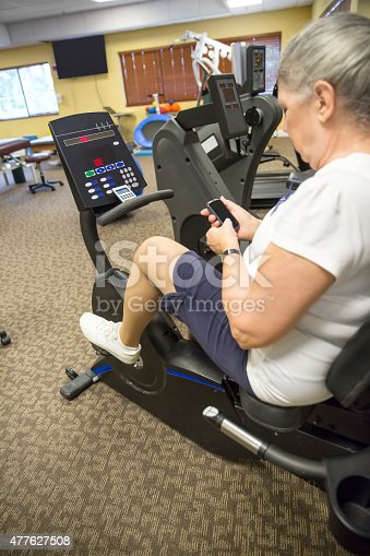 912333752 istock photo Senior caucasian woman uses cell phone while on stationary bike 477627508