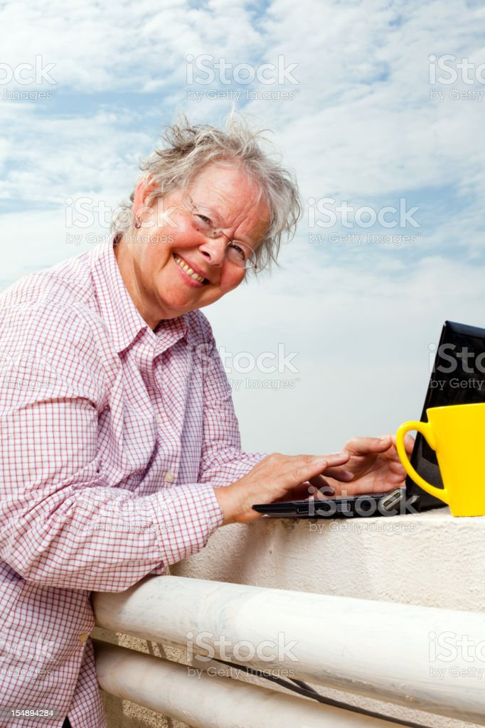 Senior Caucasian Working on Laptop Vertical Outdoor Portrait stock photo