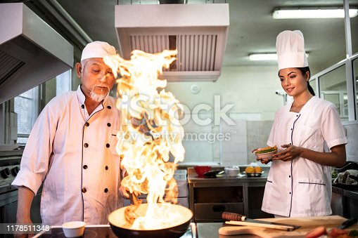Chef cooking in asian restaurant, with his female assistant, burning.