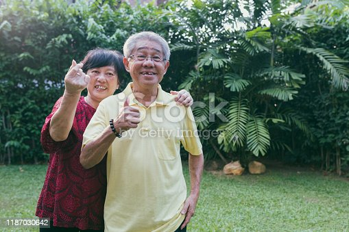 Senior chinese asian couple showing love sign in courtyard