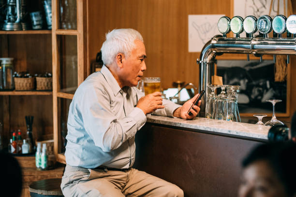 Senior Chinese Man Hangout Drinking beer in Pub Image of Senior Chinese Man Hangout Drinking beer with mobile phone in Pub. old man working in a pub stock pictures, royalty-free photos & images