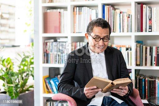 Senior Chinese man holding a book and looking at camera.