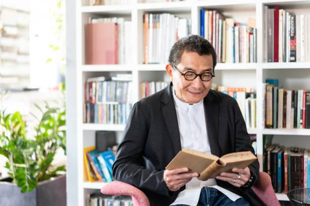 Senior Chinese man reading a book stock photo