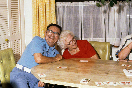A horizontal image of cheerful senior citizens who are playing cards at the kitchen table.  They are both laughing and leaning in together. It is a genuine happy and cheerful image.