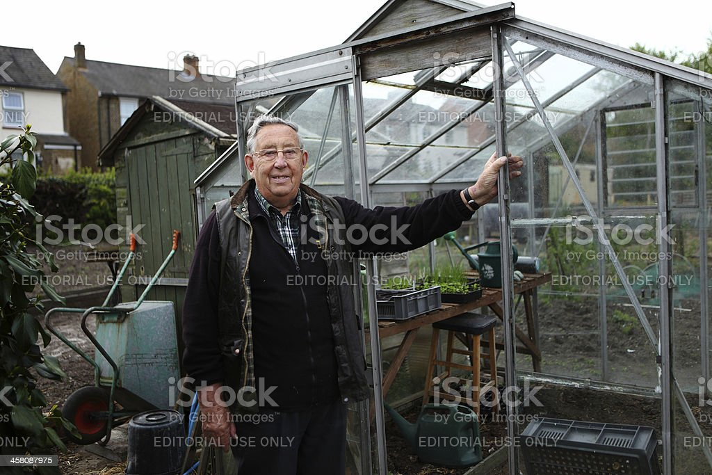 Senior citizen in front of his greenhouse royalty-free stock photo