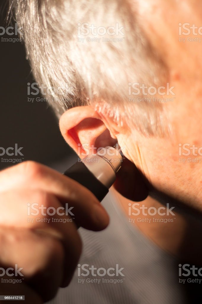 Senior citizen man cutting inner ear hair with electric cutter. zbiór zdjęć royalty-free