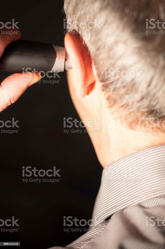 Senior citizen man cutting inner ear hair with electric cutter. zbiór zdjęć royalty-free