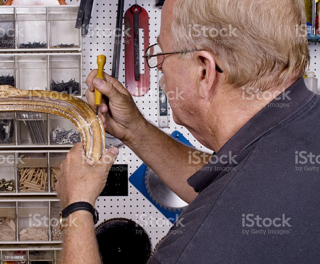 Senior citizen repairing an antique chair royalty-free stock photo