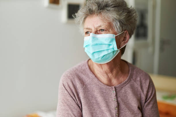 a senior citizen sits alone on her bed with a respirator or surgical mask - mask stock pictures, royalty-free photos & images