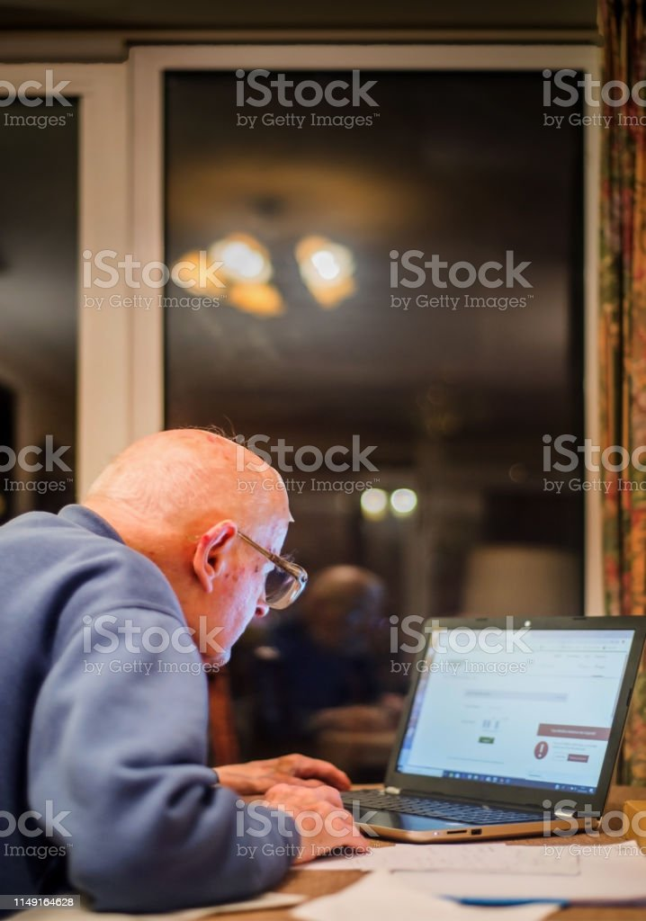 An old man of 93 years having trouble using his computer to check his...