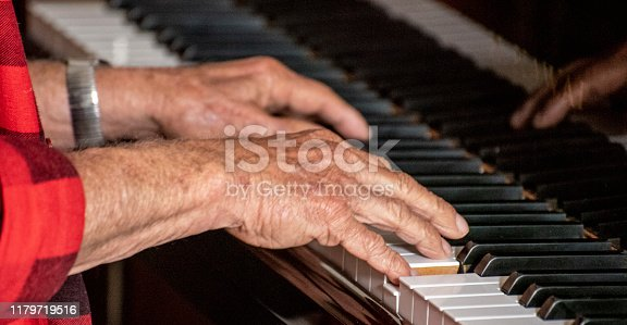 Senior citizen's hands playing the piano.