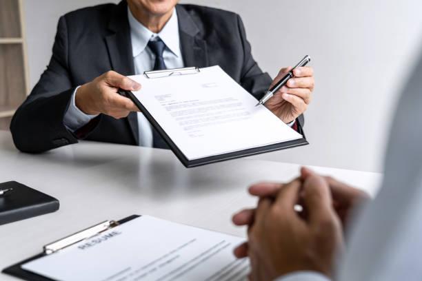 Gerente del comité sénior leyendo un CV durante una entrevista de trabajo, Entrevista del empleador para pedir al joven solicitante de empleo masculino para el reclutamiento hablando en la oficina - foto de stock