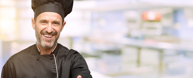 istock Senior cook man, wearing chef hat holds hands welcoming in handshake pose, expressing trust and success concept, greeting 1041973192
