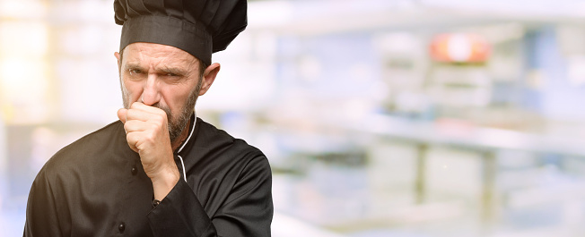 istock Senior cook man, wearing chef hat sick and coughing, suffering asthma or bronchitis, medicine concept 1041973186