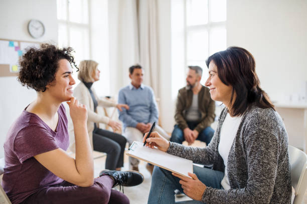 Senior counsellor with clipboard talking to a woman during group therapy. stock photo