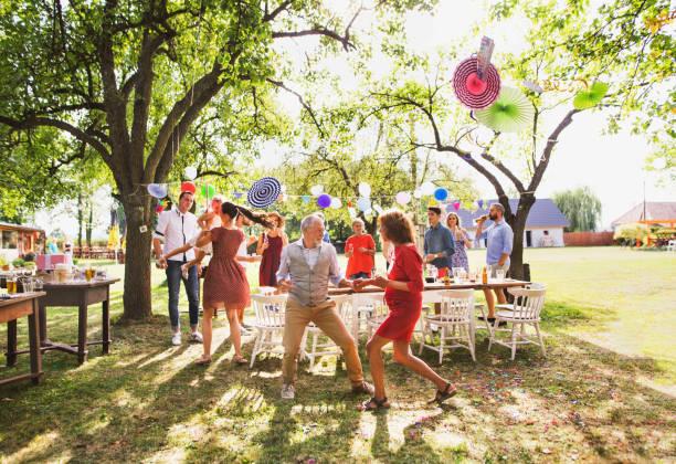 um casal sênior e família dançando em uma festa no jardim lá fora no quintal. - festa no jardim - fotografias e filmes do acervo