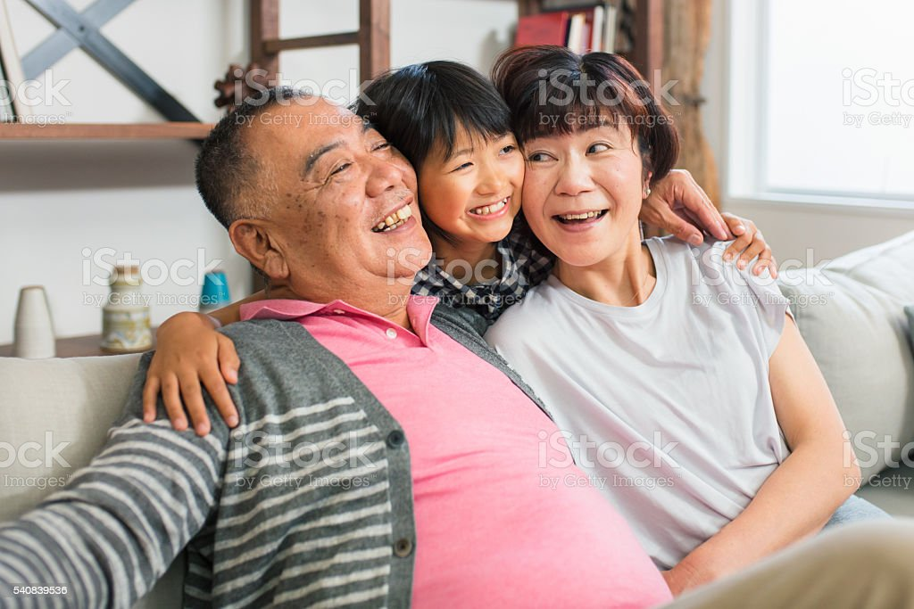 Senior couple and granddaughter hugging stock photo