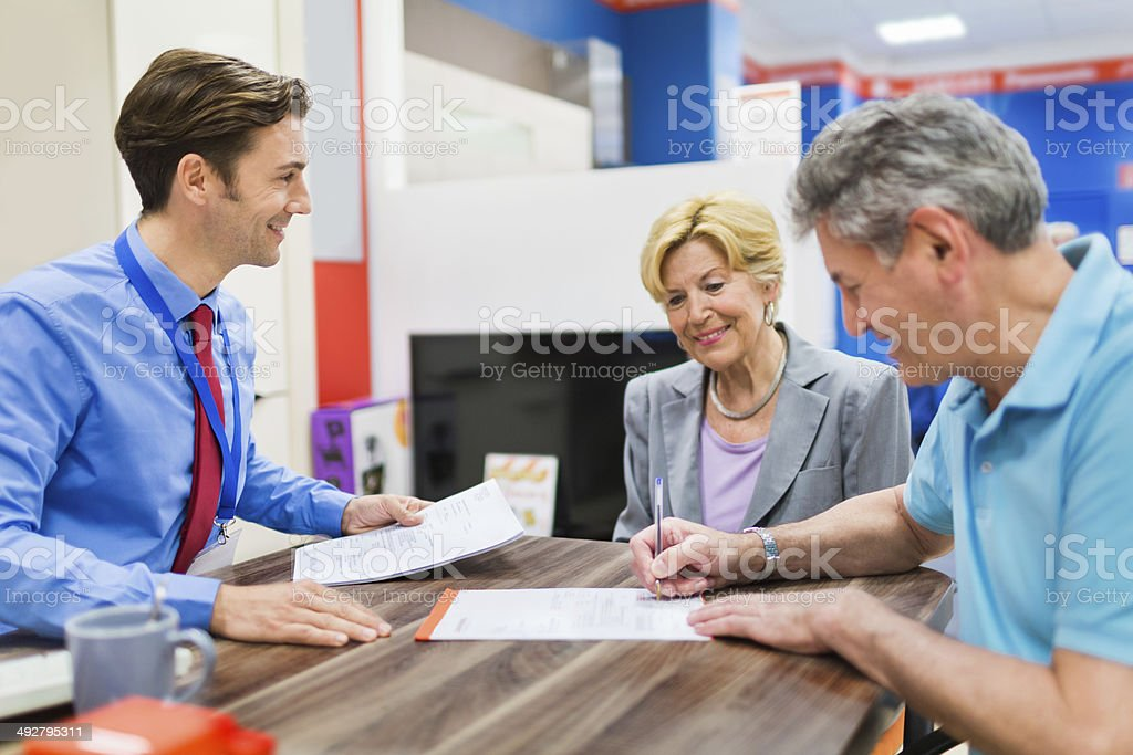 Senior Couple And Happy Salesman Signing Contract stock photo