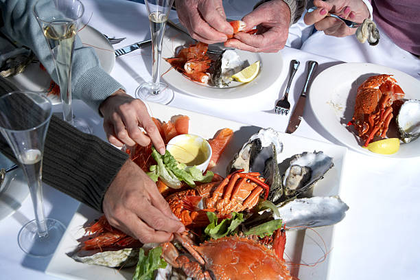 Senior couple and mature couple having shellfish lunch, close-up stock photo