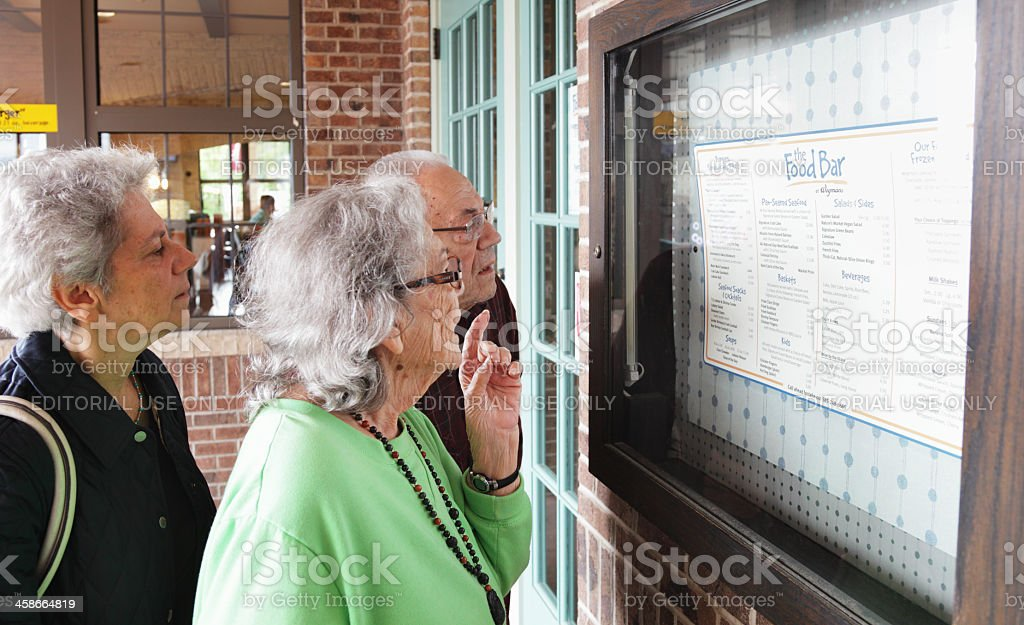 Senior Couple and Mature Woman Reading Outdoor Restaurant Menu stock photo