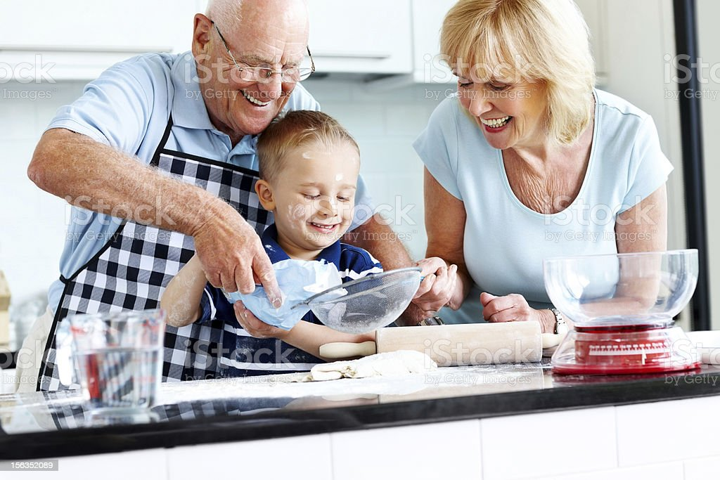 Senior couple and small kid preparing food royalty-free stock photo