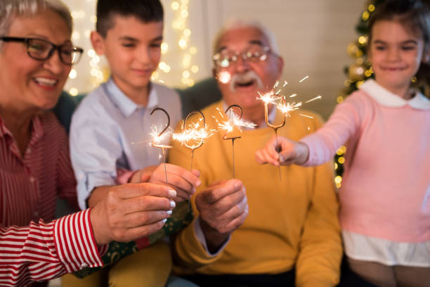 Senior couple and their grandchildren celebrating new year's eve together stock photo