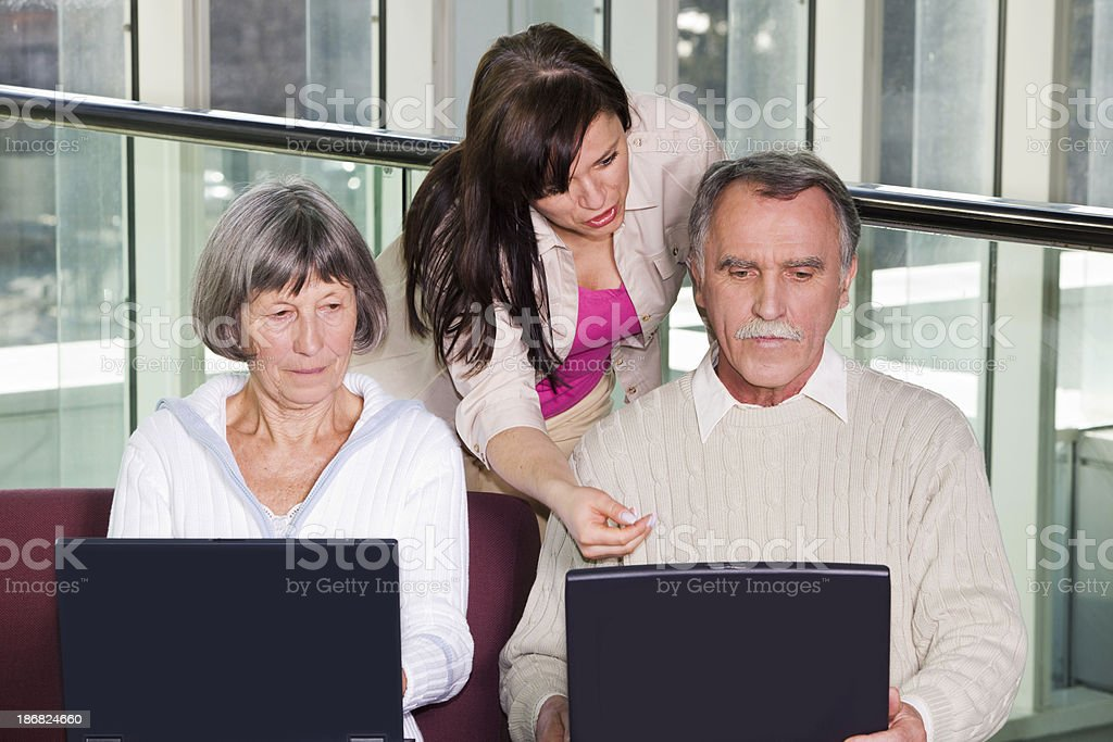Senior couple and young woman having fun with two laptops stock photo