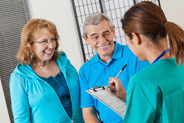 senior couple answering questions as nurse fills out patient chart - question mark asking doctor nurse stock photos and pictures