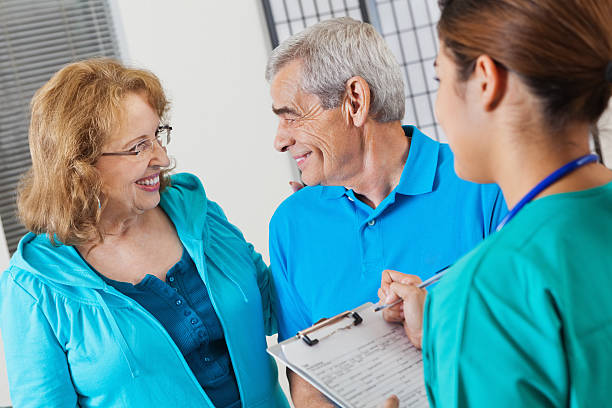 senior couple answering questions as nurse fills out patient form - question mark asking doctor nurse stock photos and pictures