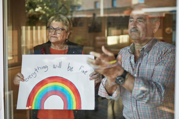 Senior couple applauding and showing a hand drawn rainbow at home in quarantine stock photo