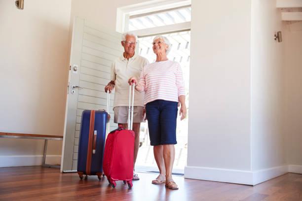 älteres paar ankunft im sommer ferienwohnung - seniorenwohnungen stock-fotos und bilder