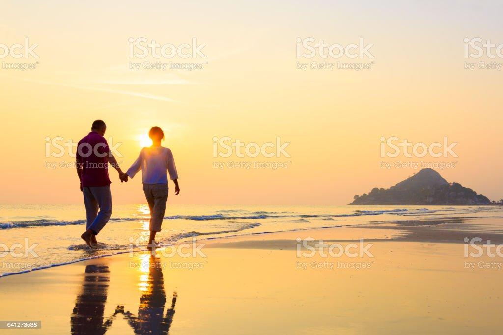 Senior couple at golden beach stock photo