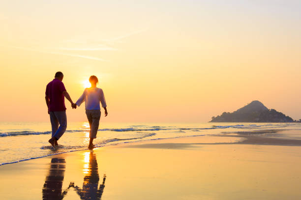Senior couple at golden beach stock photo