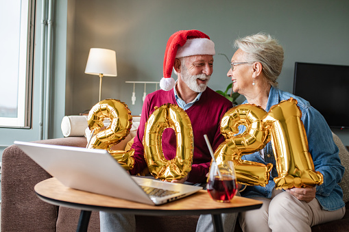 Senior couple is at home, they are sitting in the living room, holding 2021 numbers and celebrating on a video call