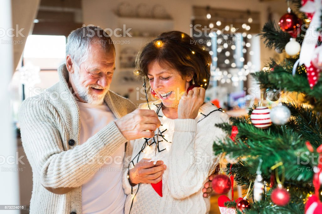 Beautiful senior couple in white woolen sweaters decorating Christmas...