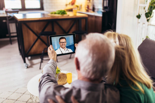 Senior couple at home holding digital tablet during video call with family doctor stock photo